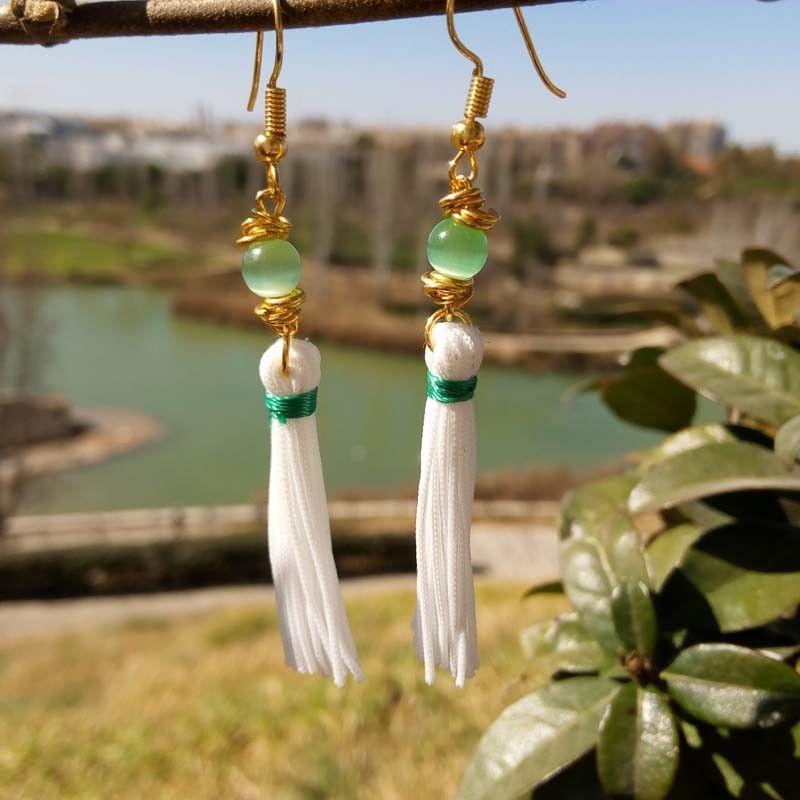 98ec61ad3818 Estos pendientes de borlas hechos a mano proporcionan un look bohemio y  moderno. Combinan cristal irisado con reflejos color verde